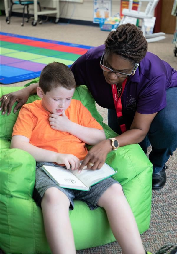 image of volunteer reading with elementary student